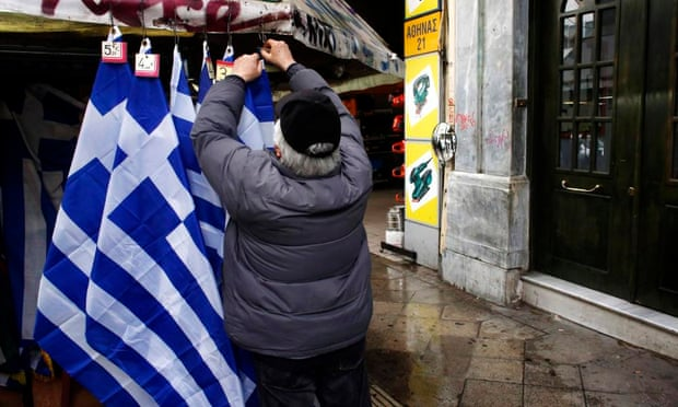A street vendor places price tickets on Greek national flags in Athens.