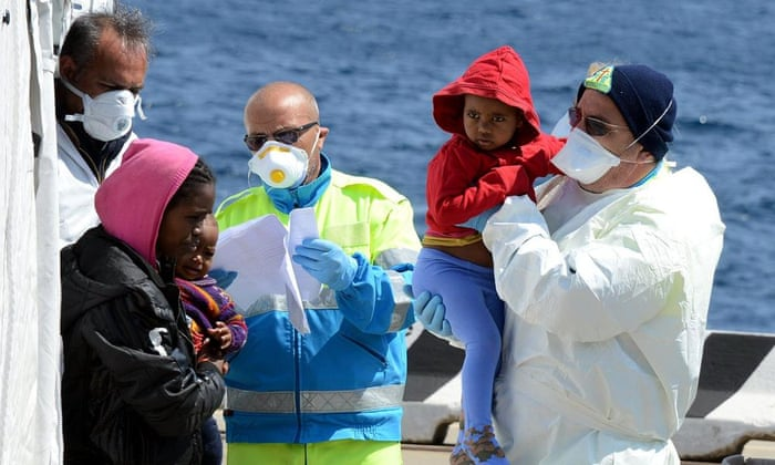 Italian Red Cross operators give first aid to immigrants as they arrive in Messina, Sicily.
