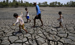 A father and his children walk over a dried out fishery near Manila