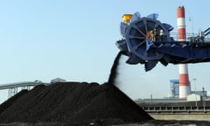 workers use heavy machinery to sift through coal at the Adani Power company thermal power plant at Mundra some 400kms from Ahmedabad