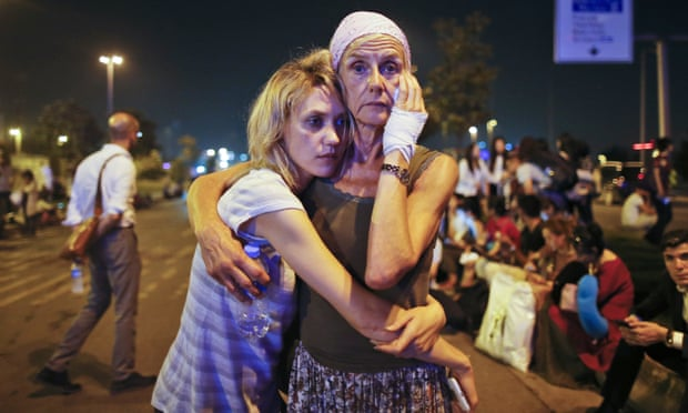 Passengers embrace each other as they wait outside Istanbul's Ataturk airport. Photograph: Emrah Gurel/AP