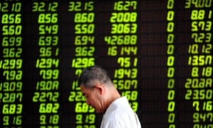 An investor walks past a stock screen in Shenyang, capital of northeast China's Liaoning Province, July 30, 2015.