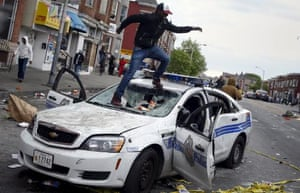 A demonstrators jumps on a damaged Baltimore police department vehicle during clashes in Baltimore.