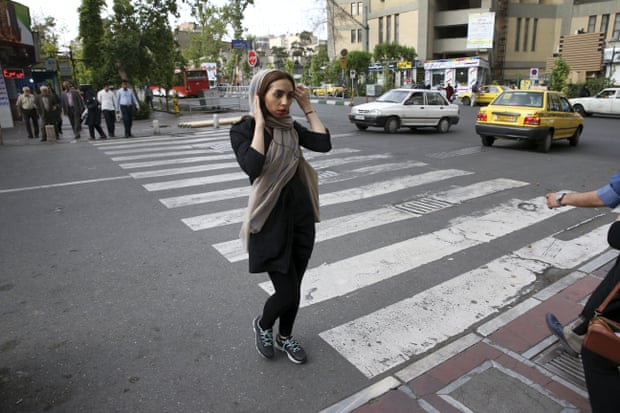 An Iranian woman adjusts her head scarf while crossing a street in downtown Tehran, Iran. Photograph: Vahid Salemi/AP