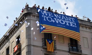 A group of people throw ballots for the referendum in Sant Jaume Square in Barcelona.
