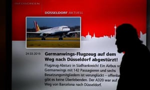 A man walks past a screen displaying news of the crash at the airport in Düsseldorf, where the Germanwings plane was due to land.