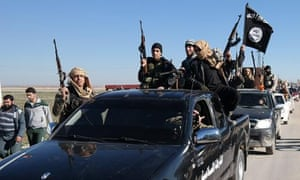 Islamic State militants pass by a convoy in Tel Abyad town, northeast Syria.