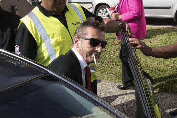 Phil Rudd flanked by security as he leaves court on Tuesday.