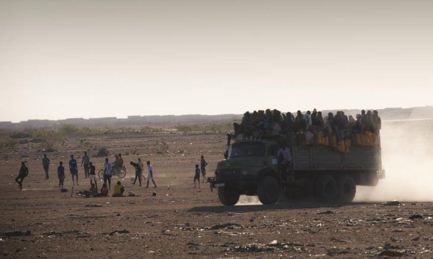 Migrants cross the Sahara desert on a truck.