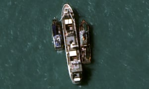 A 14 July 2015 satellite image provided by DigitalGlobe shows two fishing trawlers load slave-caught fish onto the Silver Sea 2, centre
