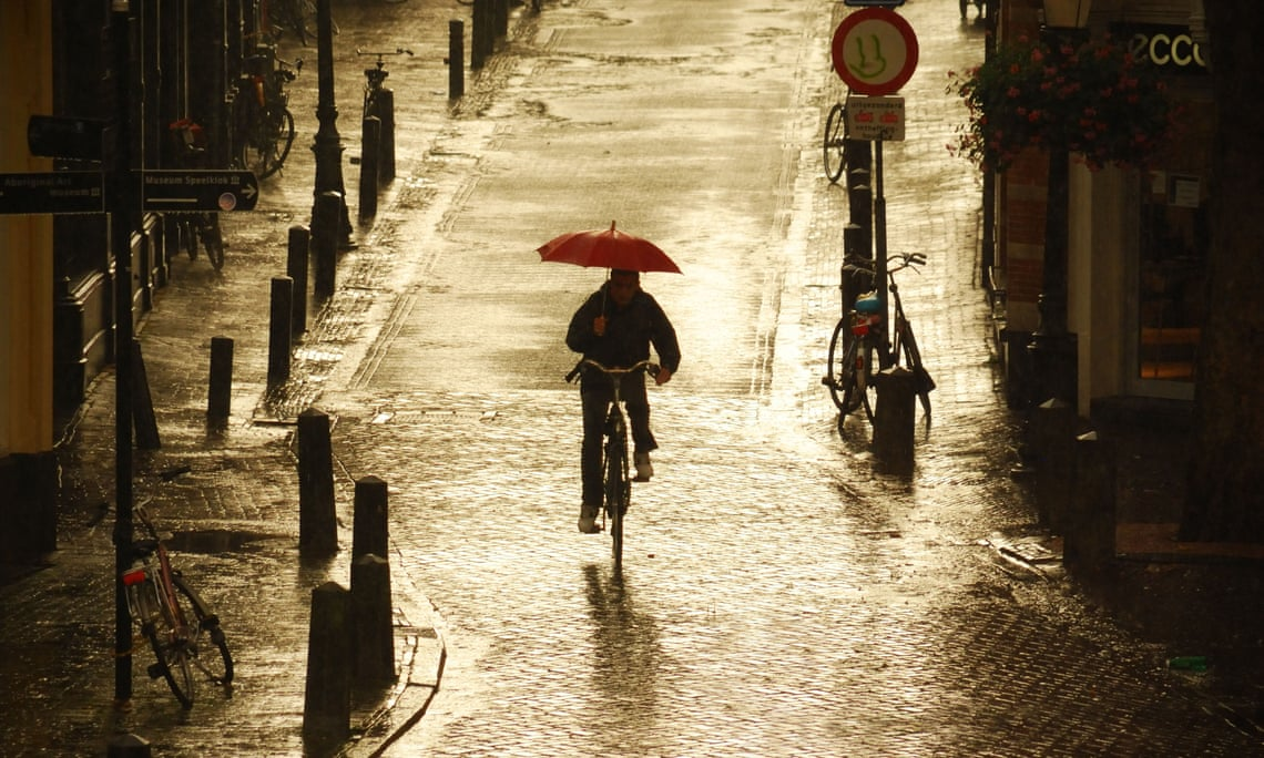 A cyclist rides in the rain in Utrecht, where 60% of city centre journeys are made by bike. Photograph: Sait Izmit/Getty Images/Flickr Open