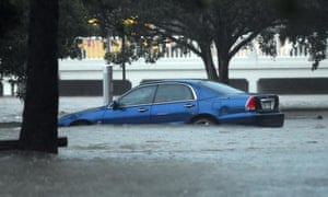 A car is submerged in flood water in Stones Corner, Brisbane.