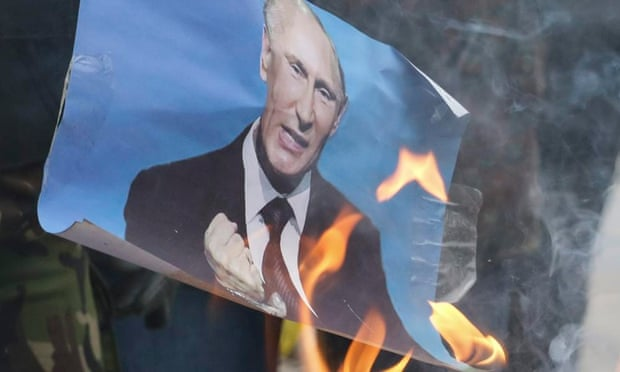 Protesters burn a portrait of Vladimir Putin at a memorial march for Boris Nemtsov, in Mariupol, Ukraine.