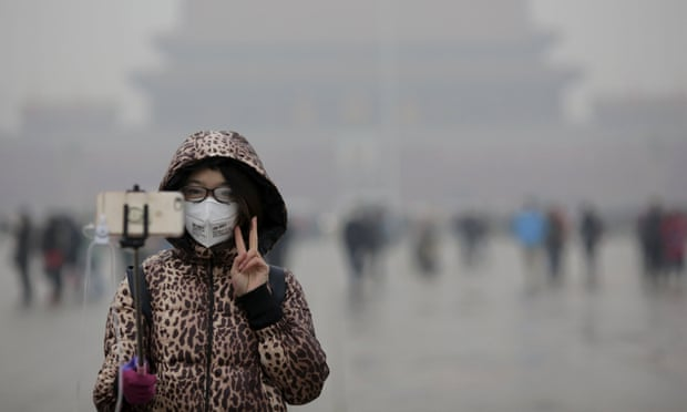 """A young woman stands amid heavy smog in Tiananmen Square, after the city issued its first ever """"red alert"""" for air pollution in December, 2015. Severe air and water pollution in China is being linked to an increase in cases of cancer and other serious health problems. Photograph: Damir Sagolj/Reuters"""