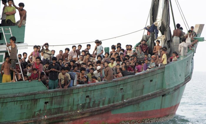 Migrants sit on a boat as they wait to be rescued by Acehnese fishermen on the sea off East Aceh, Indonesia.