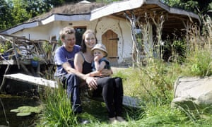 Charlie Hague, Megan Williams and their child outside their house.