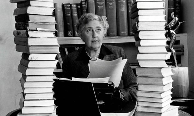 Agatha Christie sitting at her desk with books piled high. Poison was a favourite weapon in her books.