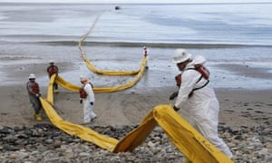 Workers prepare an oil containment boom at Refugio state beach in California.