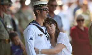 A Royal Australian Navy sailor and his partner listen to The Last Post during the Canberra ceremony.