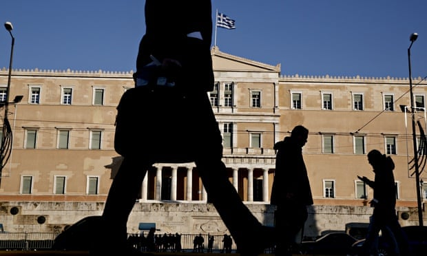 Pedestrians walks past the Greek parliament in central Athens