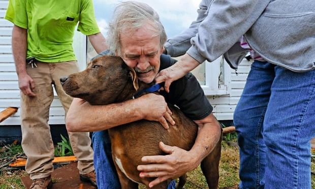 Greg Cook, 59, hugs his dog Coco after a tornado destroys his home in Alabama, 2012