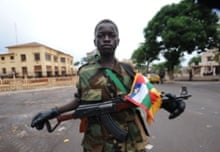 A child soldier: Seleka coalition rebel stands near the presidential palace in Bangui. The UN Security Council will hold urgent talks after a bloody coup in Central Africa sent ousted leader Francois Bozize fleeing across the border, and left 13 South African soldiers dead.