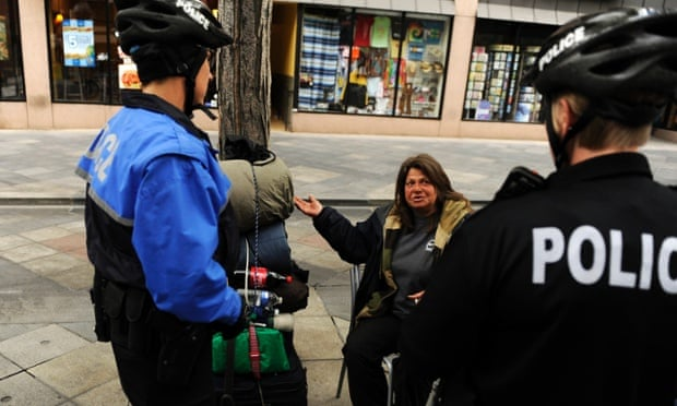 Two Denver police officers from the homeless outreach unit talk to a woman at the 16th Street Mall.
