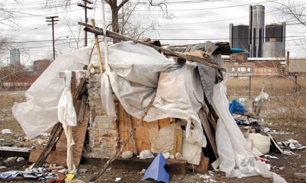 The GM headquarters building looms behind a homeless shanty in Detroit, Michigan
