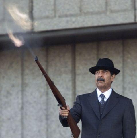 Saddam Hussein fires a rifle