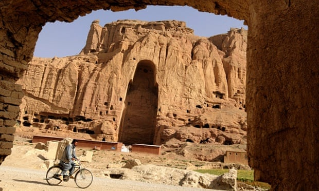 An Afghan man rids his bicycle in front of the empty seat of the Buddha destroyed by the Taliban.
