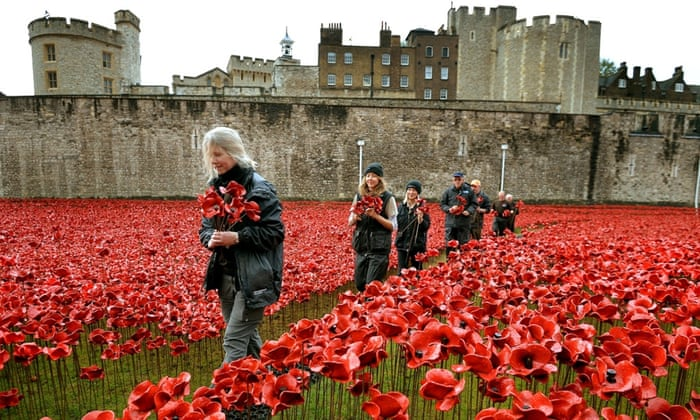 A group of volunteers remove poppies from the moat of the Tower of London, as work begins dismantling the 'Blood Swept Lands and Seas of Red' installation which captured the imagination of Britain as it commemorated the centenary of the First World War