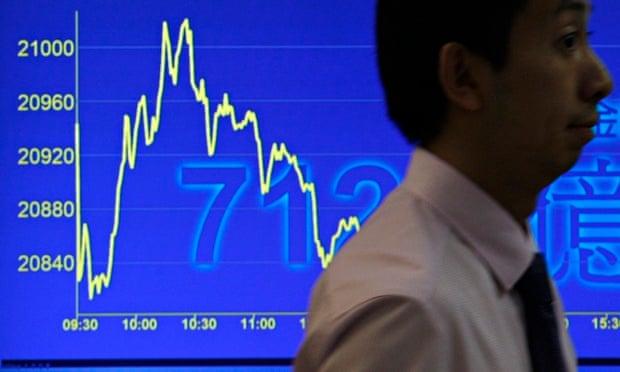 A man walks past a television monitor showing a drop in Hong Kong's benchmark Hang Seng Index