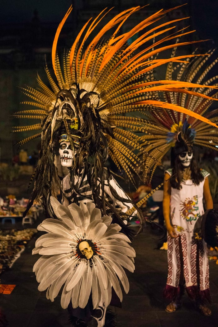 A man wears an elaborate Day of the Dead costume made from feathers and skulls