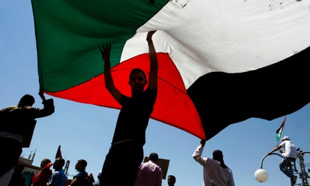 Palestinians hold a large Palestinian flag during a rally in Rafah.
