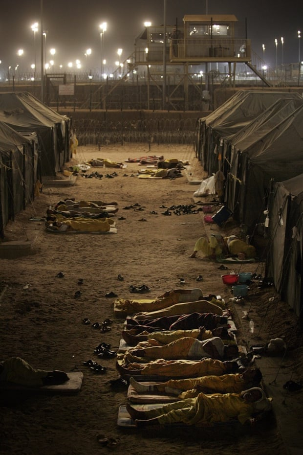 Iraqi detainees sleeping outside their tents in Camp Bucca, Iraq