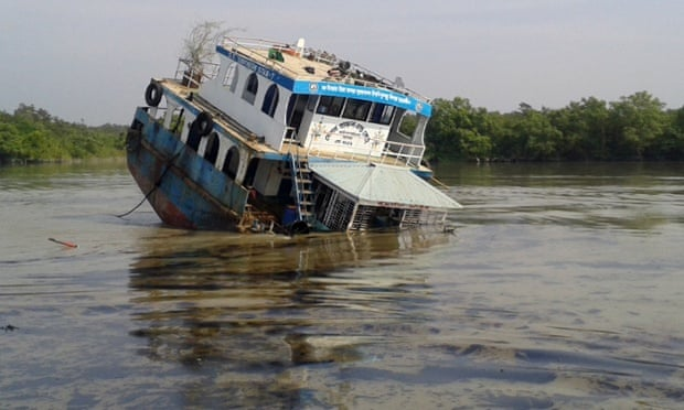 "In this photograph taken on December 9, 2014, a Bangladeshi oil-tanker lies half-submerged after it was hit by a cargo vessel on the Shela River in the Sundarbans in Mongla. Bangladesh officials warned December 11 that an oil spill from a crashed tanker is threatening endangered dolphins and other wildlife in the massive Sundarbans mangrove region, branding the leak an ecological ""catastrophe""."