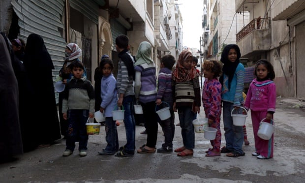 Syrian children queue for food aid from a community kitchen in the Myassar district of Aleppo.