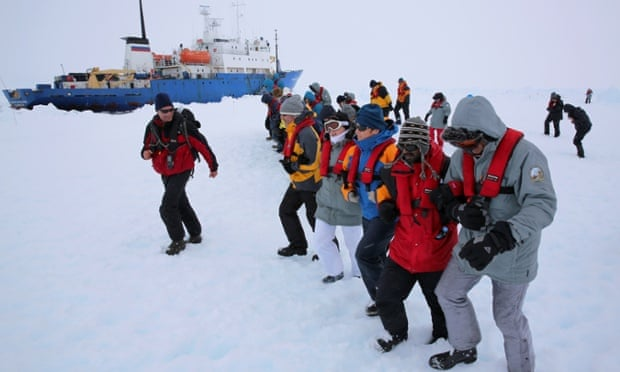 Passengers and scientists stomp an area of ice next to the Akademik Shokalskiy for a makeshift helicopter landing pad in readiness for evacuation from the trapped ship in Antarctica.