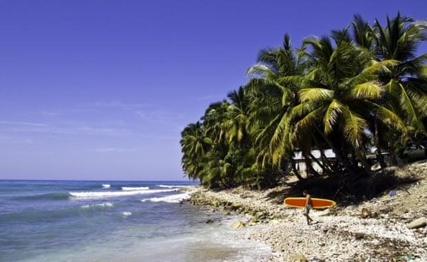 Haiti, Caribbean Sea, man with surfboard.