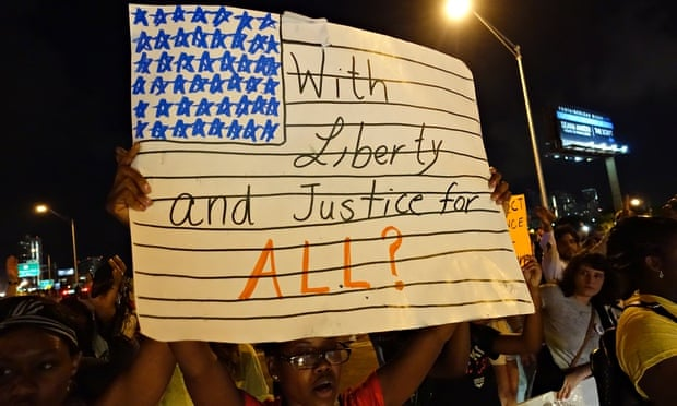 A woman holds a placard in Miami during a protest against police killings