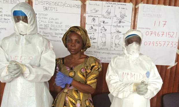 Matron Safula Mansaray instructs the white suit-clad recruits in the 'Ebola pose'