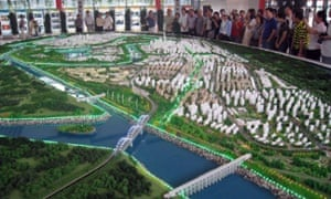 Visitors look at a model of Tianjin's eco-city. Once finished it will cover 30 km sq and house 350,000 people.