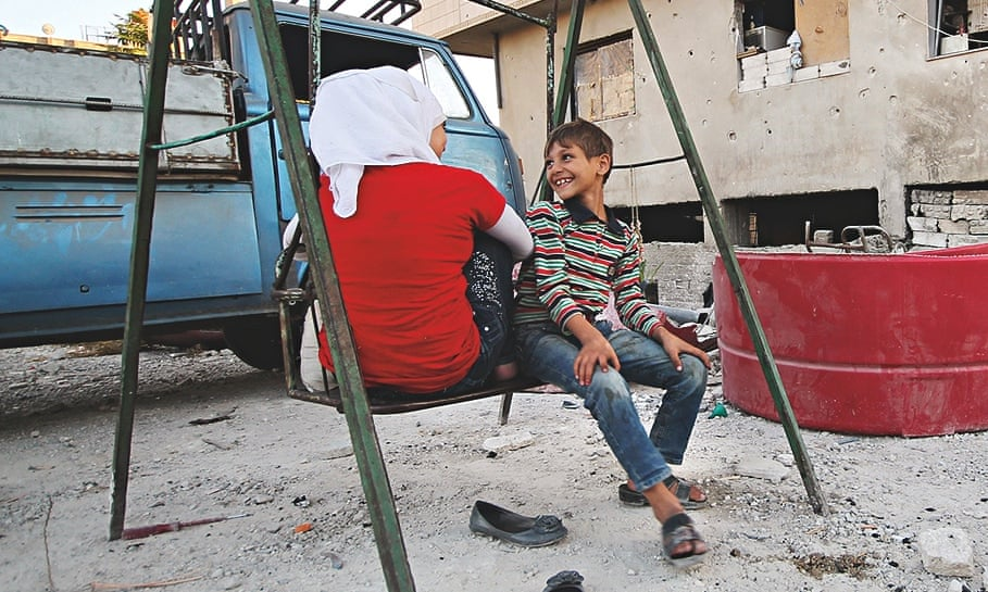 Children play on a swing in Jobar, a suburb of Damascus