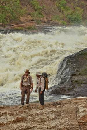 Levison Wood and his guide Boston stand at the top of Murchsion Falls. The River Nile squeezes through a gap of six metres and drops forty metres to create one of the most epic sights on the whole course of the river and is called Murchsion Falls, named after the president of the Royal Geographical Society at the time when Samuel Baker first caught sight of the falls.  Levison is attempting to be the first person to ever walk the enitre length of the Nile. He is 1500km in of a 6500km total journey and started in Rwanda. He is expecitng to finish in Egypt before December 2014. Africa Big Five Lake Albert Lev Wood Levison Wood Murchison Falls National Park River Nile Safari Tom McShane Photography Uganda Uganda Wildlife Authority Walk The Nile Walkiing the Nile Water Waterfall