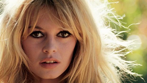 Primo piano del viso radioso di Brigitte Bardot degli anni verdi: capelli biondi che scendono fino alle spalle, sorriso appena pronunciato, occhioni scuri splendidi.