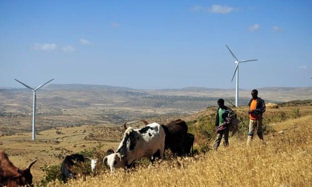 Men walk along a road near turbines
