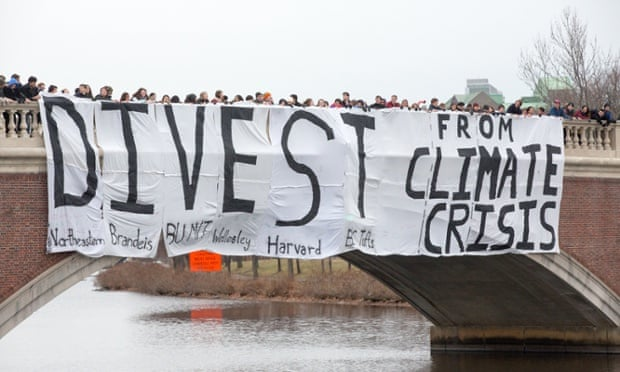 "A ""Divest from climate change"" banner is dropped over the Charles River by Boston students who aim to stop climate change by having their schools divest from the fossil fuel industry, 8 December 2013 ."