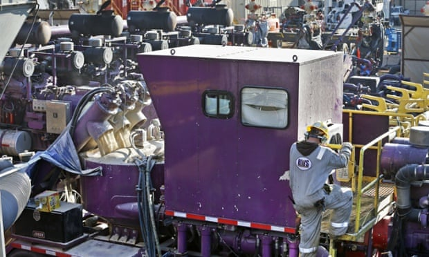 A machine mixes sand, water and chemicals before it is pumped underground during a fracking operation at a drilling site.