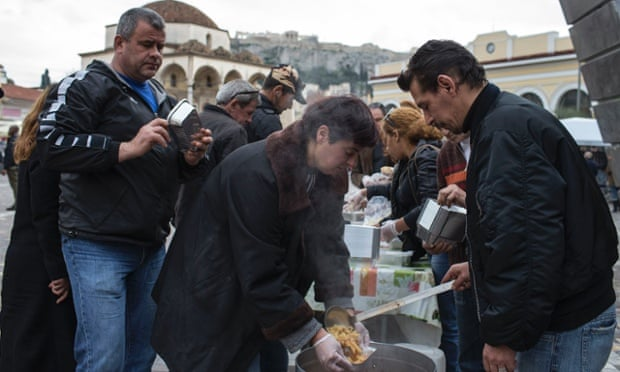 People queue for food at a soup kitchen in Athens.