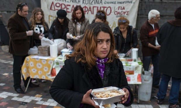 A woman takes away a portion of food from a soup kitchen in Athens.